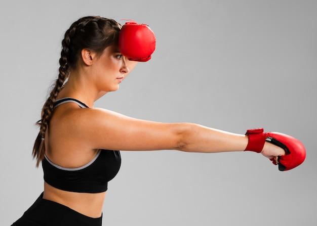 Chica de costado golpeando con guantes de box