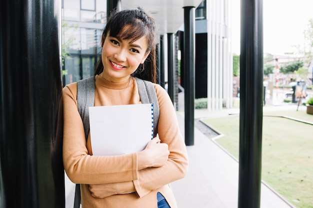 Chica con cuaderno sonriendo a la cámara