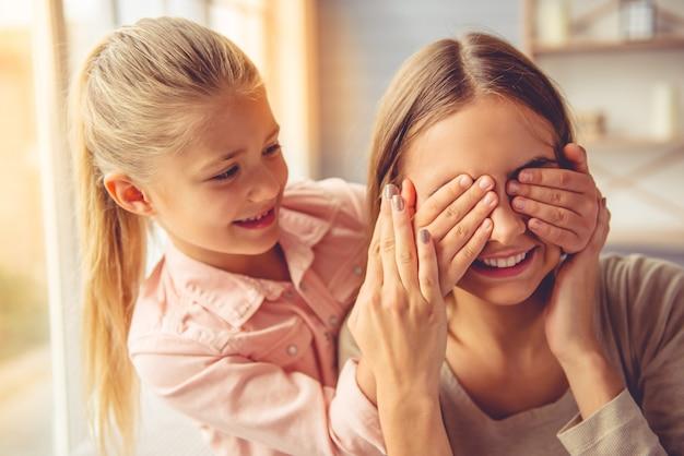 Chica está cubriendo los ojos de mamá en casa