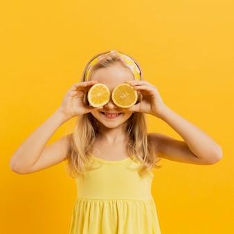 Chica cubriendo los ojos con rodajas de limón