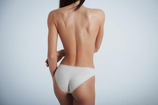 Chica con cuerpo perfecto en ropa interior blanca dando la espalda