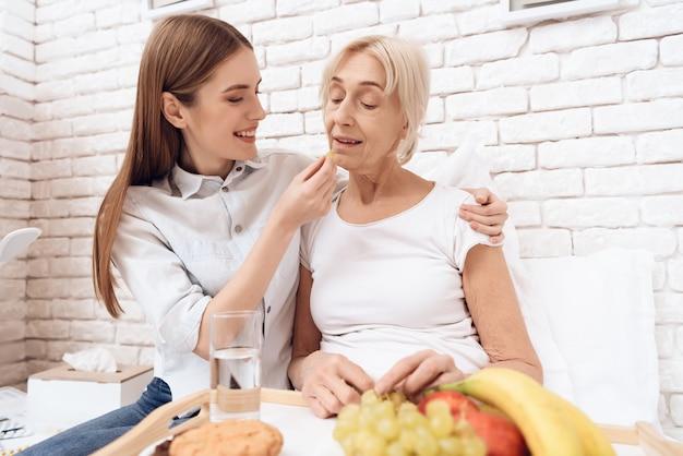Chica cuida a una anciana en casa.