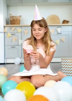 Chica de cumpleaños de tiro completo con cupcake