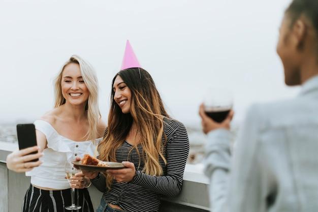 Chica de cumpleaños tomando un selfie con su amiga en una azotea