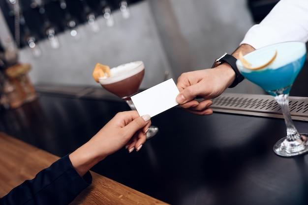 La chica le da al barman el pago de la orden.