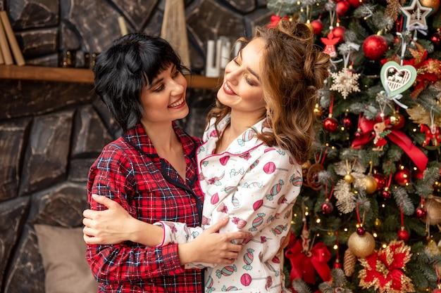 Chica dando un regalo de navidad a su novia. se abrazan cerca del árbol de navidad y se ven muy felices.
