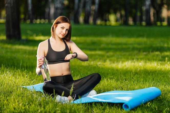 Chica de deporte usando rastreador de fitness o monitor de ritmo cardíaco con una botella de agua
