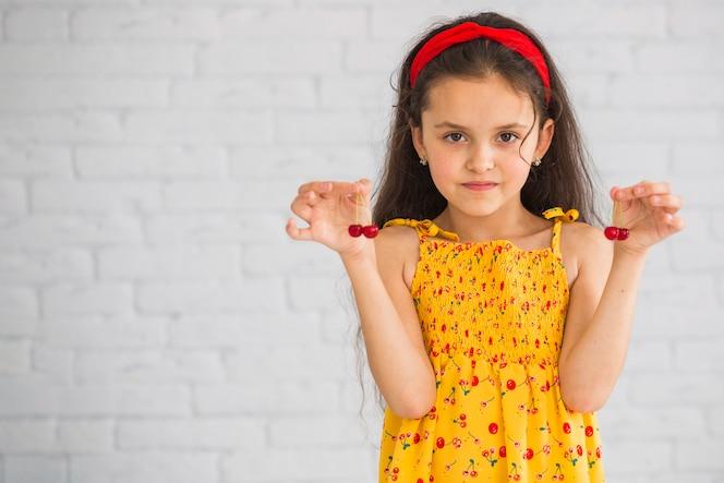 Chica de pie delante de la pared con cerezas rojas en la mano