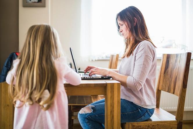 Chica de pie delante de su madre trabajando en la computadora portátil