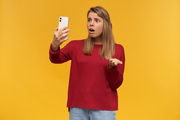 Chica decepcionada mantiene el teléfono móvil en la mano, mirándolo como si estuviera haciendo una videollamada, abrió la boca como si fuera incomprendida
