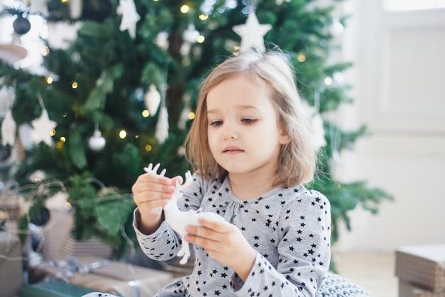 Chica decorando la casa con árbol de navidad y decoración navideña.