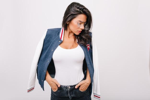 Chica delgada de cabello oscuro en camiseta blanca mirando hacia abajo tomados de la mano en el bolsillo. retrato de interior de modelo de mujer morena con gafas y chaqueta de bombardero de moda.