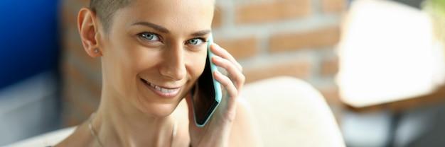 Una chica delgada con un corte de pelo corto habla por teléfono mientras está sentada en un sofá. moda joven sonriendo mientras escucha al interlocutor en el teléfono inteligente