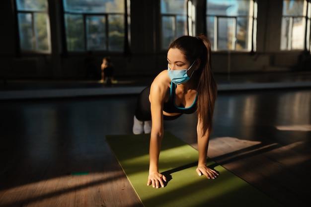 Chica delgada con máscara para proteger la pandemia de la enfermedad covid-19 y el distanciamiento social para hacer ejercicio en casa