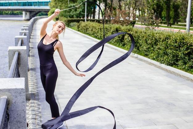 Chica delgada de moda en la calle con una cinta de gimnasia