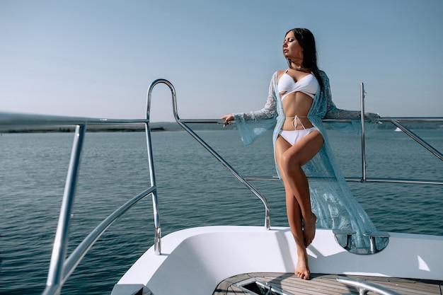 La chica delgada con los ojos cerrados en un bikini blanco de pie al borde del yate y mira a lo lejos. vacaciones de verano