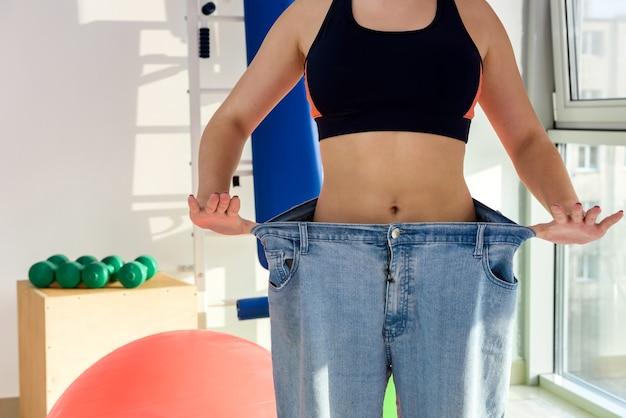 Chica delgada con pantalones de gran tamaño en el gimnasio