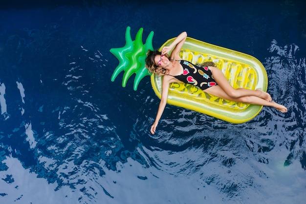Chica delgada con piel bronceada riendo mientras está acostado sobre un colchón en el balneario. foto exterior de modelo de mujer guapa con gafas de sol brillantes.