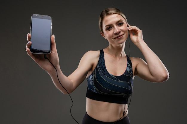 Chica delgada en un top deportivo con un teléfono y auriculares en una pared negra