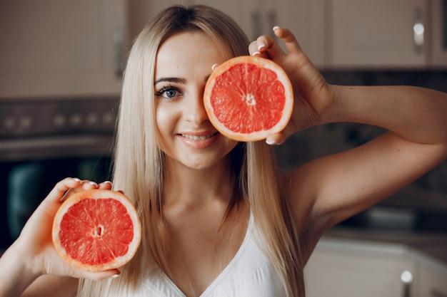 Chica de deportes en una cocina con frutas.