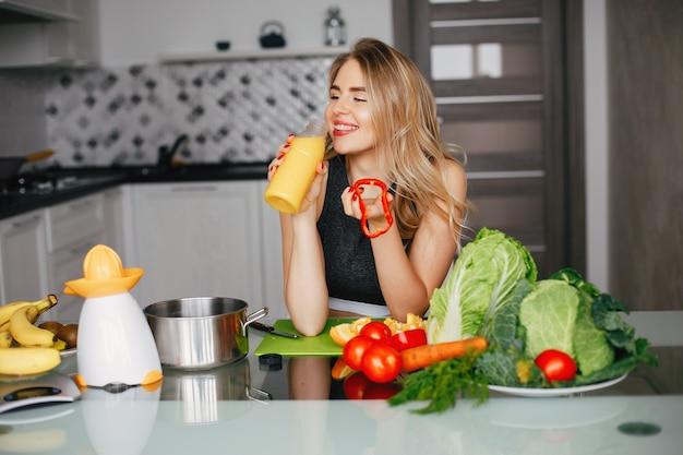 Chica de deportes en una cocina con verduras
