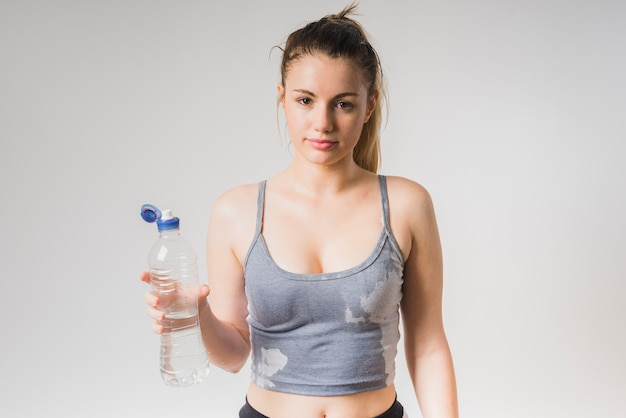 Chica deportista mojada con botella de agua