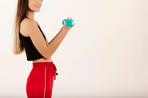Chica deportistas sonriente levantando peso