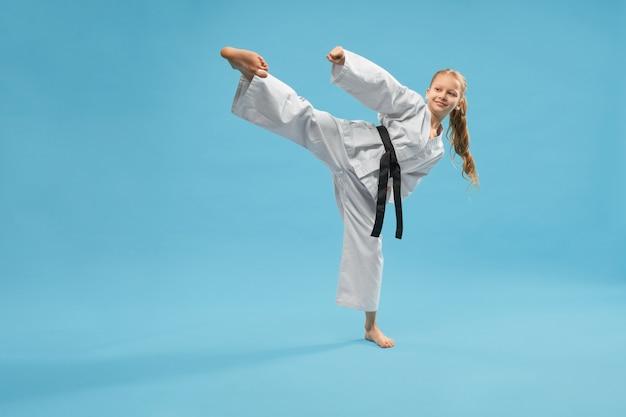 Chica deportiva activa en kimono pateando con pierna en estudio