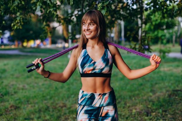 Chica deportiva atractiva se encuentra con una cuerda de saltar y felizmente sonriendo al aire libre