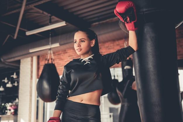 Chica deportiva atractiva en guantes de boxeo está practicando.