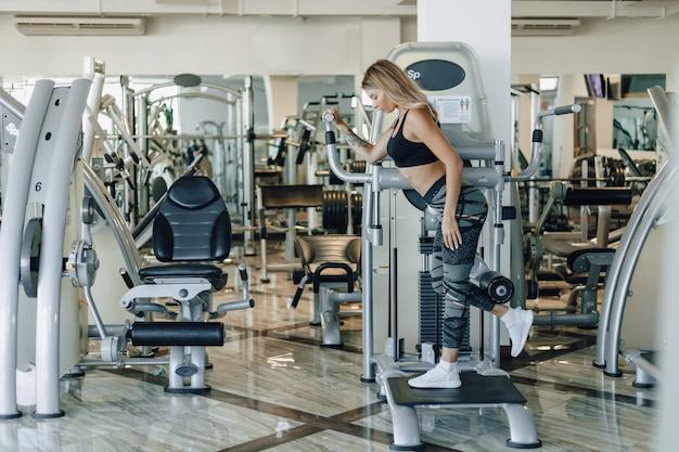 Chica deportiva atractiva realiza ejercicios en caderas y glúteos. estilo de vida saludable.