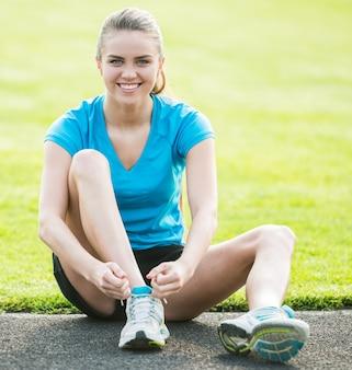 Chica deportiva atractiva sentada en la carretera y atar cordones de los zapatos