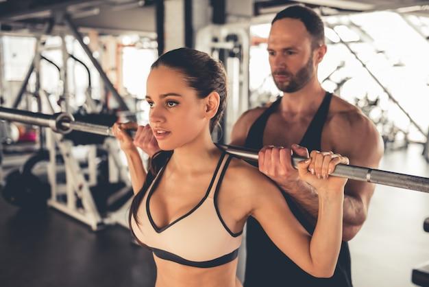 Chica deportiva atractiva está trabajando con barra en el gimnasio.