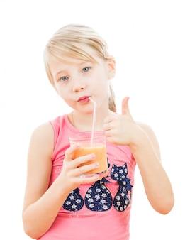 Chica deportiva está bebiendo un batido de una toronja.