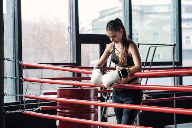 Chica deportiva cansada se apoyó en cuerdas rojas en el ring de boxeo y descansó después de un duro entrenamiento en el gimnasio loft negro. concepto de estilo de vida saludable y deportivo.