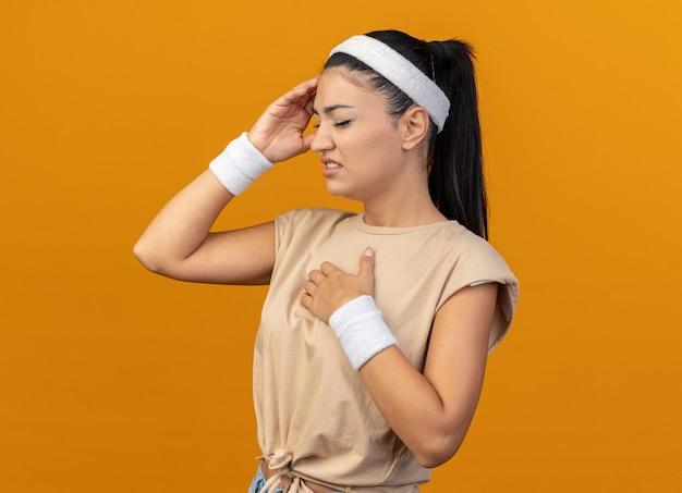 Chica deportiva caucásica joven dolorida con diadema y muñequeras de pie en la vista de perfil manteniendo la mano en el pecho tocando la cabeza con los ojos cerrados aislados en la pared naranja con espacio de copia