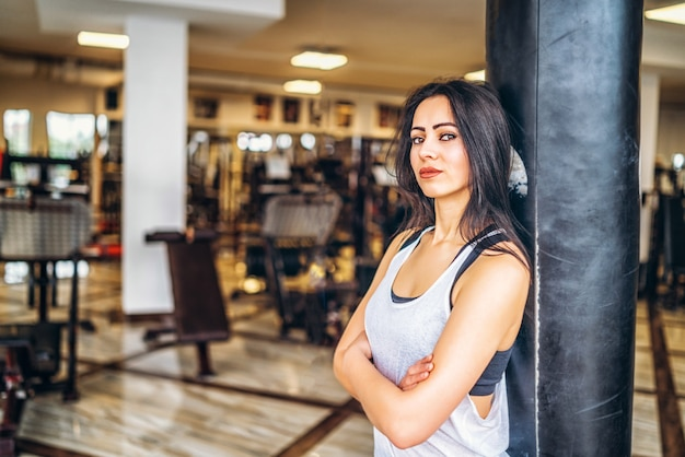 Chica deportiva cerca de saco de boxeo en el gimnasio