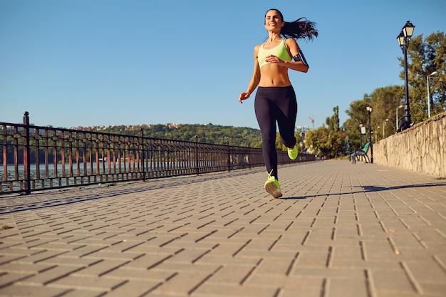 Una chica deportiva corre por el parque junto al lago.