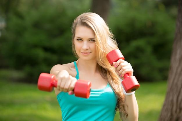 Chica deportiva ejercicio con pesas en el parque