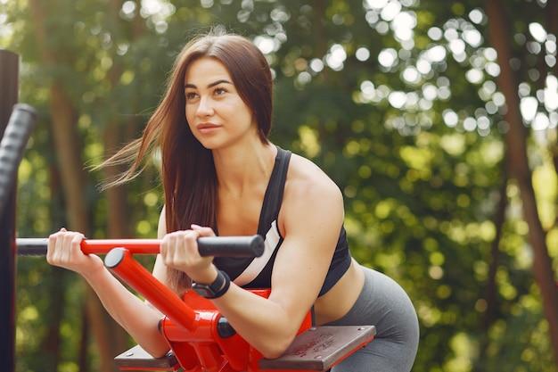 Chica deportiva en un entrenamiento top negro en un parque de verano