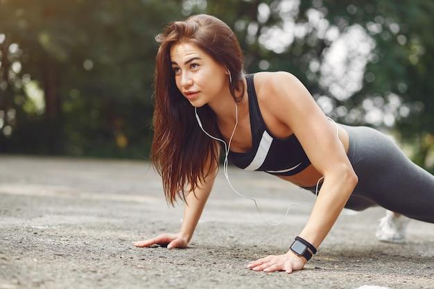 Chica deportiva entrenando con auriculares en un parque de verano