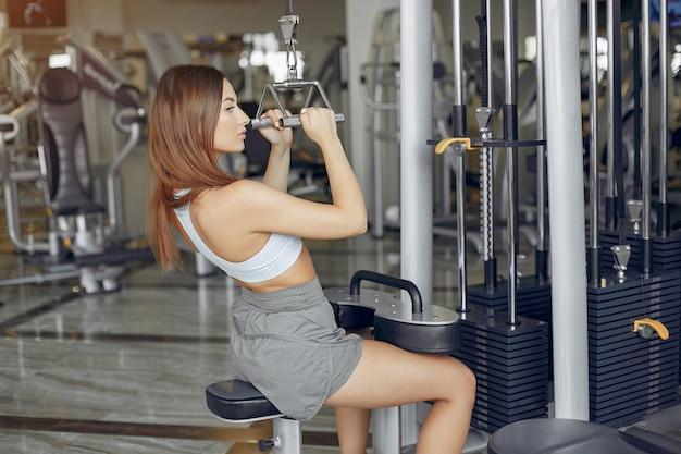 Chica deportiva entrenando en un gimnasio de la mañana