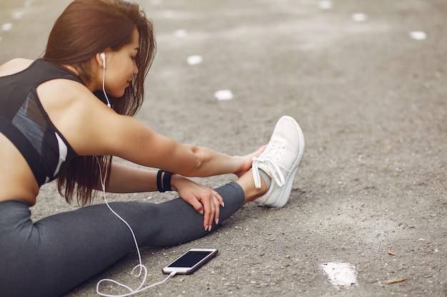Chica deportiva entrenando con teléfono y auriculares