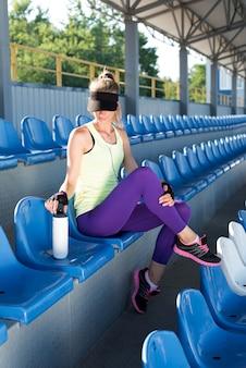 Chica deportiva en el estadio. tribuna del estadio. mujer delgada fitness deportivo. botella shaker protein. concepto de medios sociales y fitness.