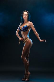 Chica deportiva fuerte y musculosa en bikini de pie y mirando a la cámara