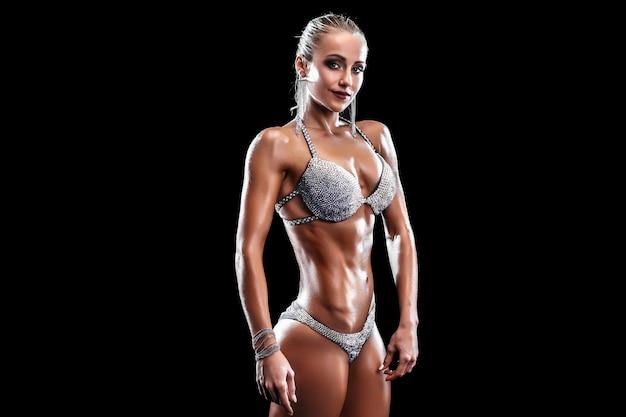 Chica deportiva fuerte y musculosa en bikini de pie
