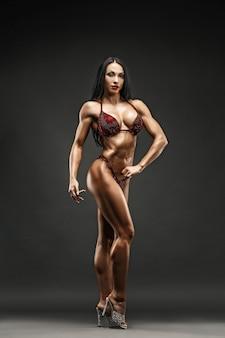 Chica deportiva fuerte y musculosa en bikini posando