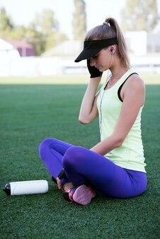 Chica deportiva habla por teléfono. estadio de fútbol. mujer delgada fitness deportivo. botella shaker protein. concepto de medios sociales y fitness.