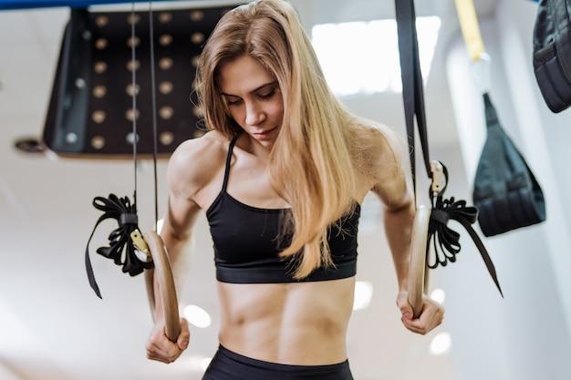 Chica deportiva haciendo estiramientos en el gimnasio con anillos y mirando hacia abajo.