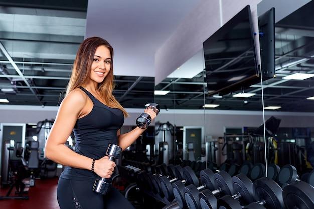 Chica deportiva con mancuernas en el gimnasio.